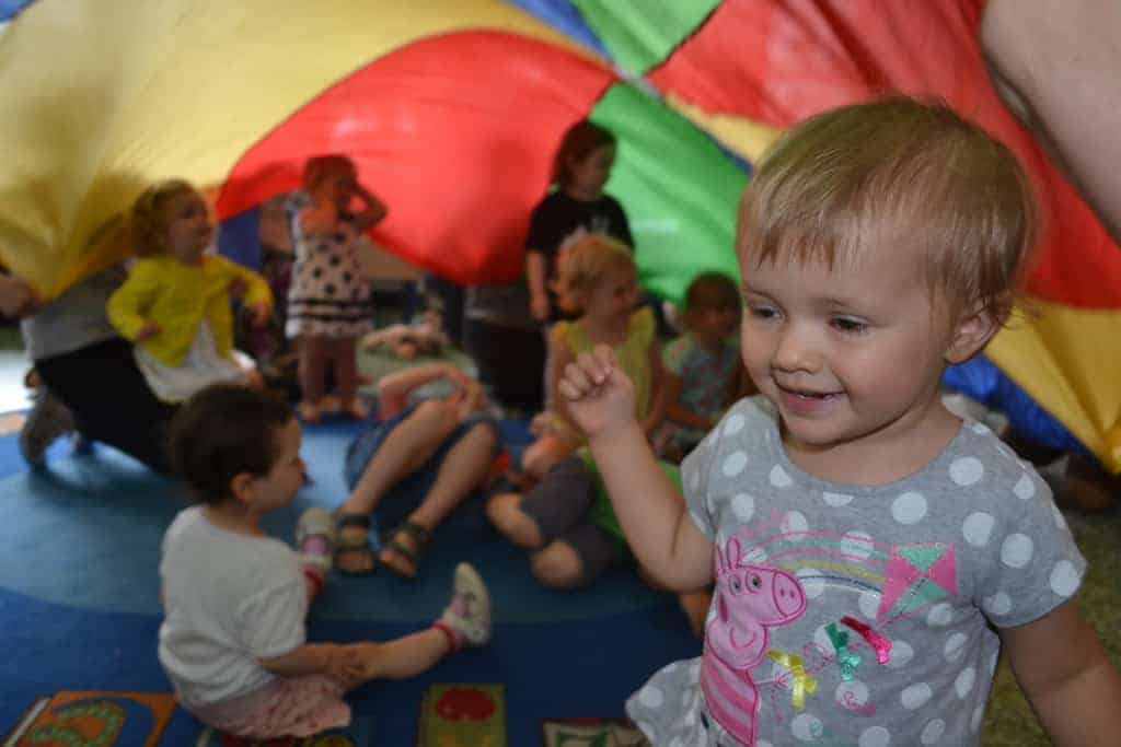 Toddler playing party parachute game